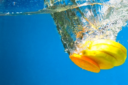 Citrus slice splashing in water with blue background Stock Photo - 15542144