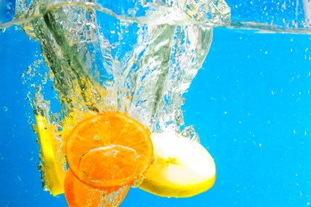 Citrus slice splashing in water with blue background photo