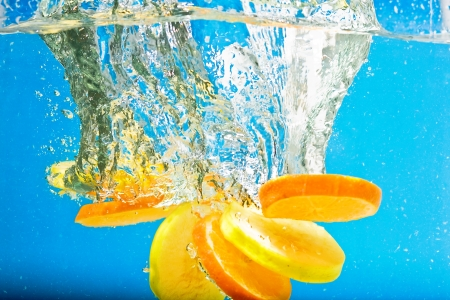 colorful water surface: Citrus slice splashing in water with blue background