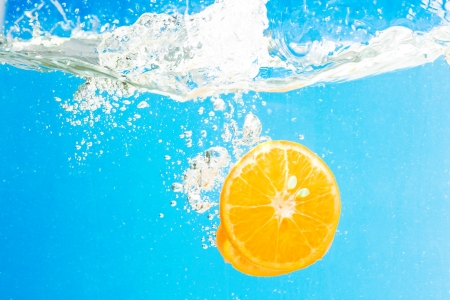 Citrus slice splashing in water with blue background Stock Photo - 15542000
