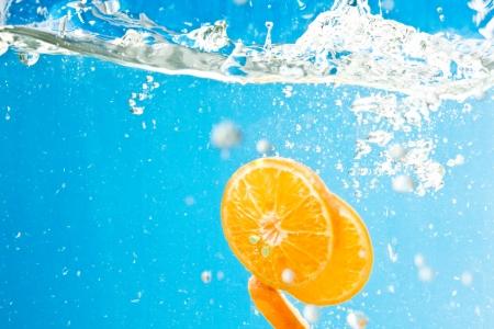 Citrus slice splashing in water with blue background photo