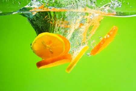 Yellow citrus splashing in water with blue background photo