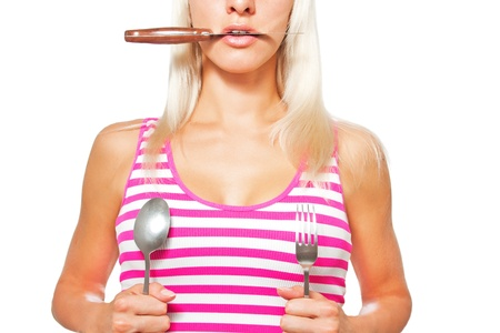 Beautiful blonde girl is preparing to eat holding cutlery items