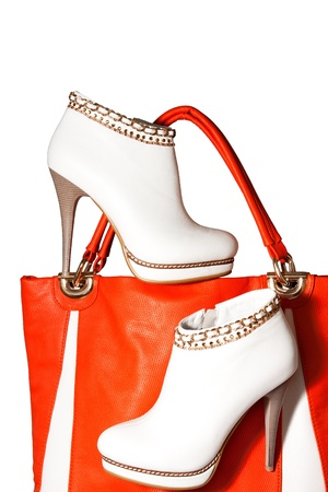 A pair of beautiful white womens ankle boots high-heeled and orange handbag photo