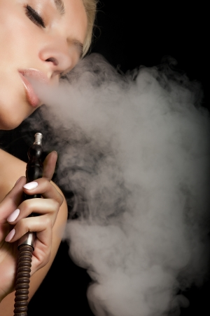 Beautiful woman smoking a hookah and smoke issues from the mouth Stock Photo