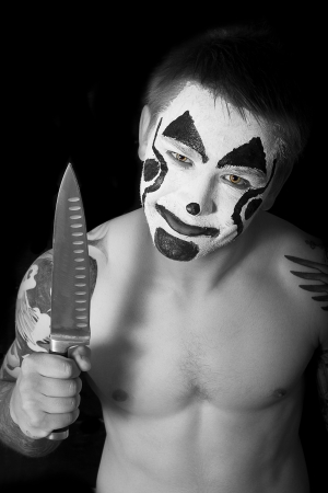 pumped up young man with tattoos and painted face with a knife photo