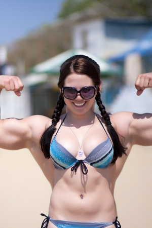 weakness: A strong girl with big muscular arms on a beach Stock Photo