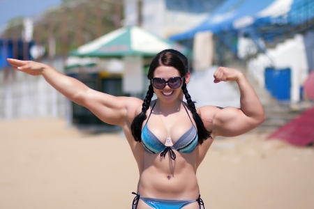 A strong girl with big muscular arms on a beach Stock Photo