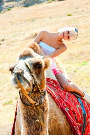 animal woman: Beautiful blonde woman riding a camel