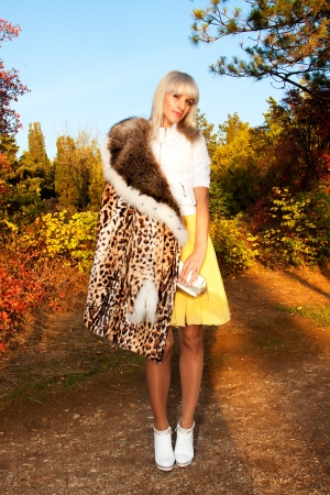 Beautiful blonde girl in leopard fur coat standing in the forest, smiling Stock Photo