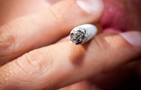 persona fumando: Sigaretty punta humeante en las manos masculinas, primer plano