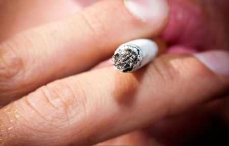 man smoking: Smoldering tip sigaretty in male hands, close-up