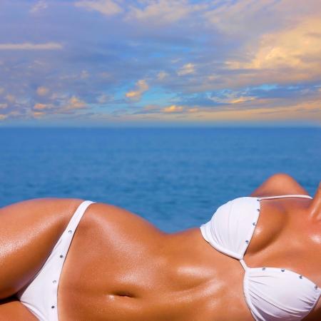 hot breast: Сексуальная молодая блондинка с красивым телом загорает на пляже в белом купальнике на фоне моря Фото со стока