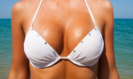 Beautiful large tan female breast in a white bathing suit against the sea