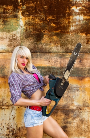 Sexy blonde girl builder with a chainsaw Stock Photo