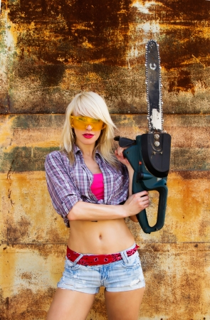 A girl with a chainsaw on a background texture rusty wall photo