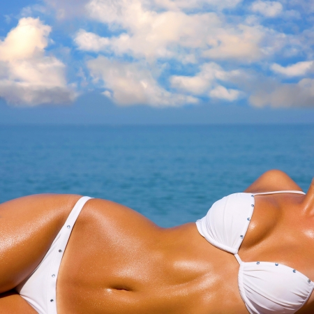 nude blond girl: The sexual young blonde girl with a beautiful body sunbathes on a beach in a white bathing suit against the sea Stock Photo