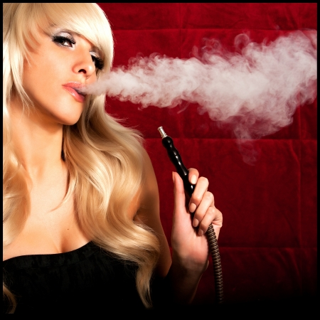 Beautiful woman smoking a hookah and smoke issues from the mouth Standard-Bild