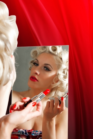 Pin up girl paints lips with red lipstick in the mirror Stock Photo - 18961885