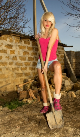 Beautiful blonde girl with an ax, chopping firewood