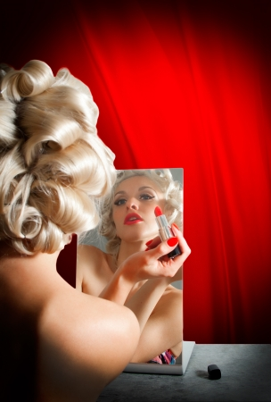Pin up girl paints lips with red lipstick in the mirror photo