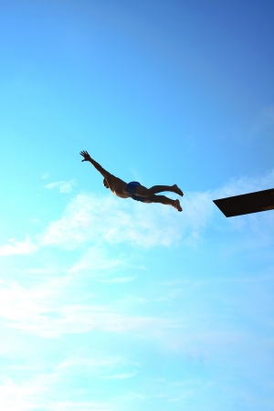 man makes a jump into the water from a springboard