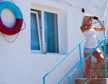 lifeguard tower: A beautiful young blond woman lifeguard watching through binoculars at the rescue station