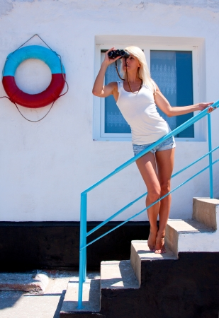 A beautiful young blond woman lifeguard watching through binoculars at the rescue station  photo