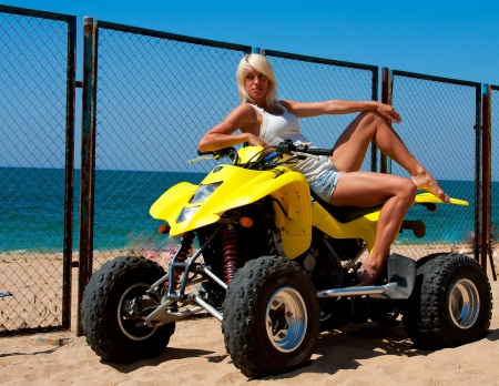 Beautiful sexy blonde on the quad on the beach photo
