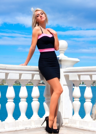 Beautiful slim blonde girl in full growth posing outdoor