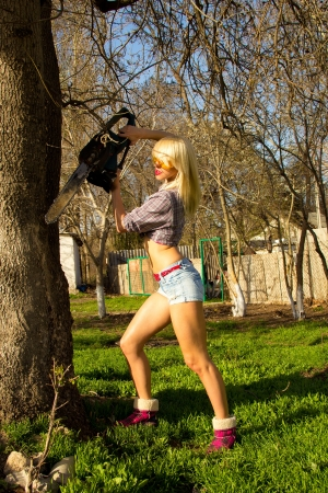 blonde girl in protective goggles sawing wood chainsaw photo