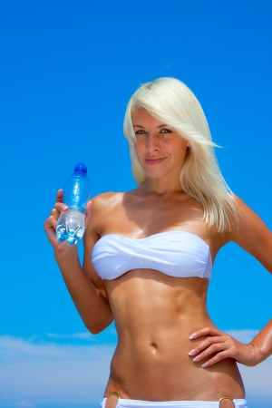 A beautiful young blonde woman drinking water at the beach photo