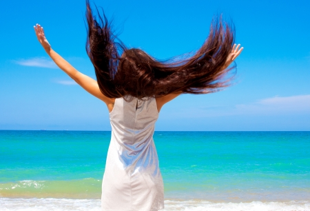 Beautiful woman with long hair at the sea