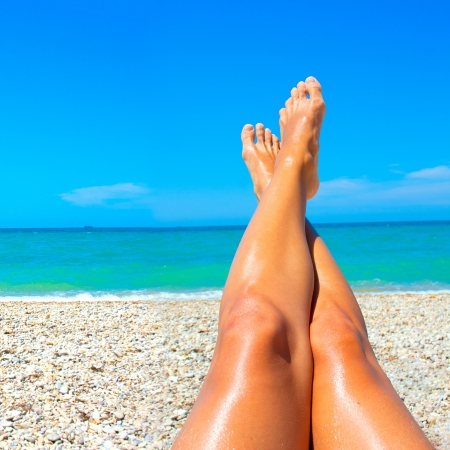long toes: Beautiful long legs tanned women on the background of the sea