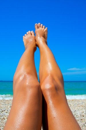 chiropody: Beautiful long legs tanned women on the background of the sea