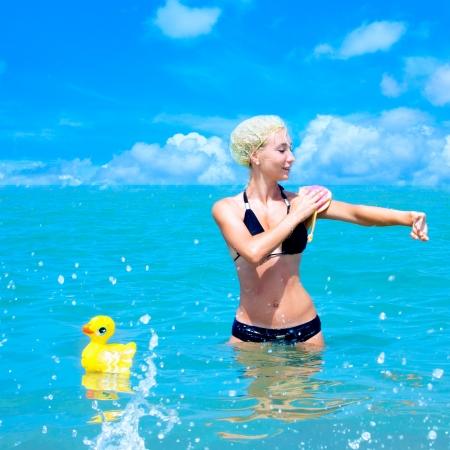 La jeune fille en maillot de bain avec un gant de toilette et un canard de jouet est lavé dans la mer, comme dans la salle de bain Banque d'images - 20646179