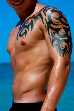 A man with a beautiful muscular body with tattoo relaxing on the beach photo