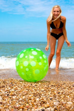 Beautiful woman on the beach playing ball photo