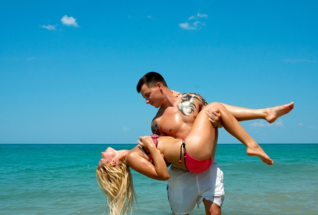 Beautiful young couple in love having fun on the beach photo