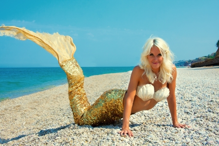 Cute attractive blonde mermaid near the sea photo