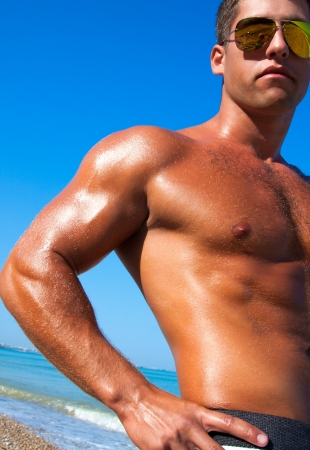 A man with a beautiful muscular body relaxing on the beach Stock Photo