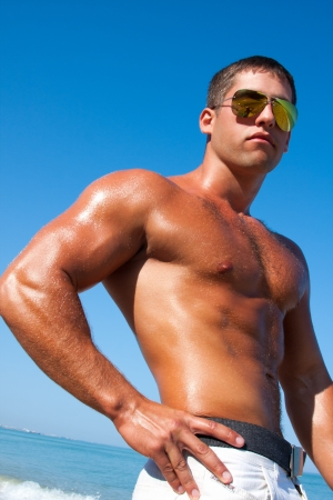 A man with a beautiful muscular body relaxing on the beach photo