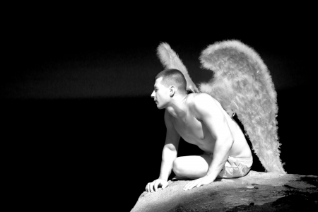 Muscular man with angel wings on the beach photo
