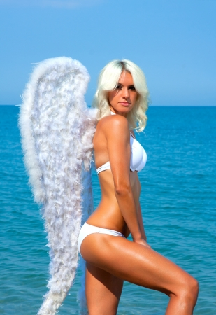 Beautiful sexy blonde woman with angel wings on the beach photo