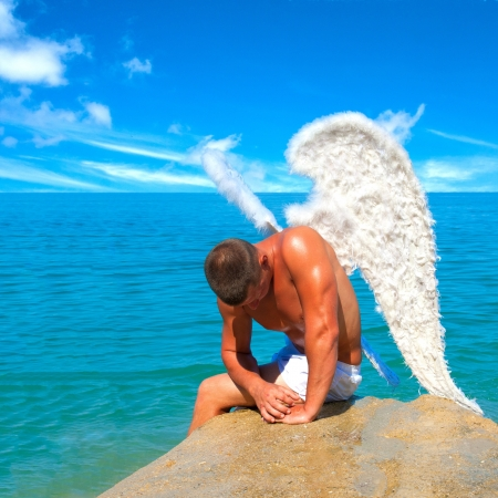 sexy angel: Muscular man with angel wings on the beach