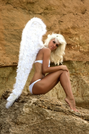 Beautiful sexy blonde woman with angel wings on the beach