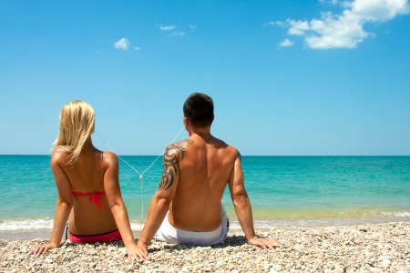 Young happy guy and girl listening to music through headphones on the beach