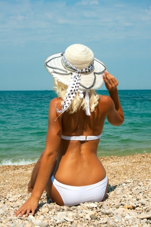 Beautiful blonde girl in hat relaxing on the beach photo