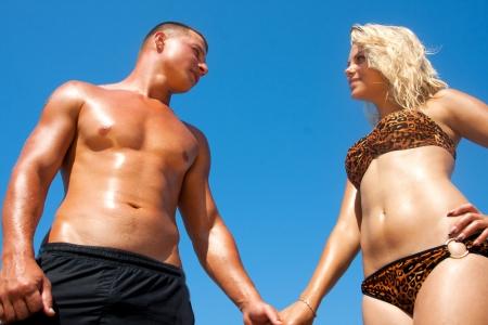 Young happy beautiful couple having fun on the beach