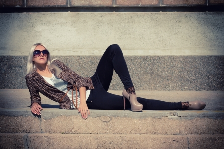 long pants: Fashion photo of beautiful slender girl model in leopard print jacket with sunglasses Stock Photo